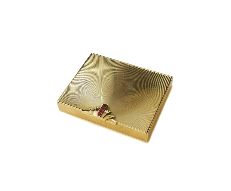 A stunning Retro compact from Tiffany & Co. The compact is made from 14kt solid yellow gold. The face of this compact has a simple design that holds four vibrant, square-cut rubies. The exterior has a carved texture which perfectly represents the