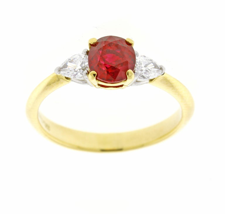 From Tiffany & Co. a Vivid  red ruby  and pear shape diamond ring. ♦  Designer: Tiffany & Co ♦  Metal: 18 karat and platinum ♦  Oval vivid red ruby=1.02 carats ♦  2 diamonds=.23 ♦ Circa 1990 ♦ Size 6, Resizable ♦ Packaging: Tiffany Box ♦ Condition: