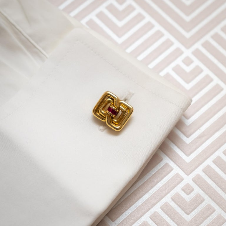 A pair of Tiffany & Co. cufflinks, with a geometric, double figure-of-eight design, with baguette-cut rubies in the centre, in channel settings, mounted in 18ct gold, with bars and tilting terminals, with a geometric, figure-of-eight design, signed