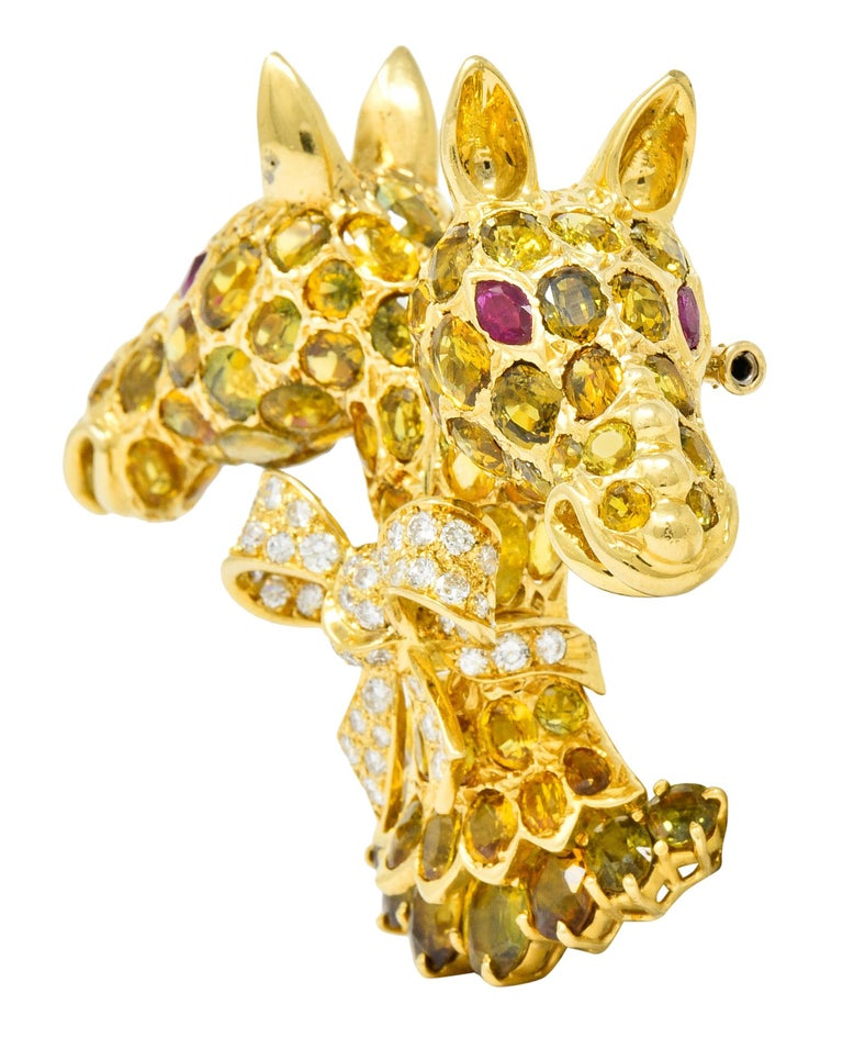 Designed as two mirrored giraffes cinched at the neck with a pavè diamond bow with a beautifully tiered base  Eyes shine bright as well-matched, deeply red, marquise cut rubies weighing approximately 0.88 carat total  Round brilliant cut diamonds