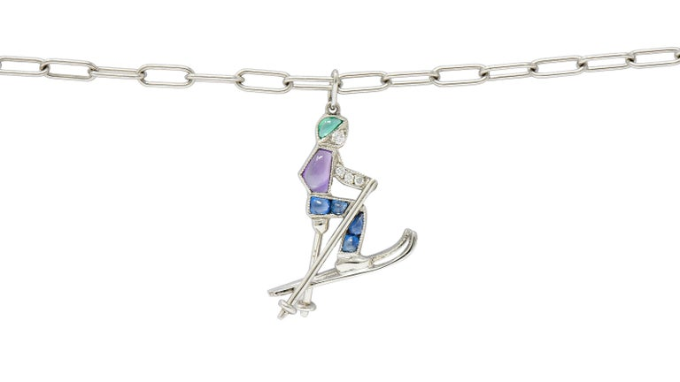 Paperclip style charm bracelet suspends a single stylized skier charm  Set with brightly colored calibre cut gemstones of sapphire, amethyst, and emerald  Accented by round brilliant cut diamonds weighing in total approximately 0.05 carat - eye