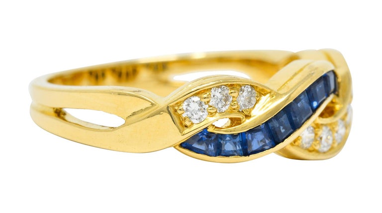 Band ring is designed as two interlaced undulating waves  One accented by bead set round brilliant cut diamonds weighing approximately 0.32 carat; F/G color with VS clarity  The other channel set with calibrè cut sapphire, well-matched, weighing