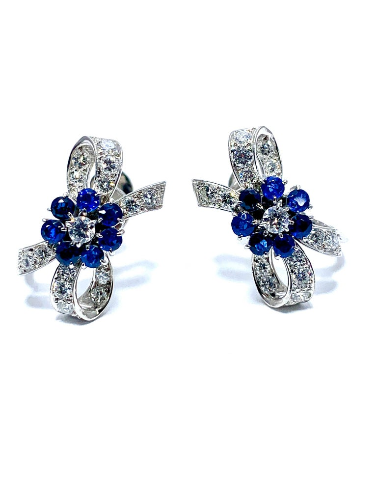A beautiful pair of Tiffany & Co. Sapphire and Diamond palladium earrings.  The Sapphires are fashioned in the shape of a flower, attached to a diamond encrusted bow , and features a screw tightened non pierced back.  There are 1.02 carats in