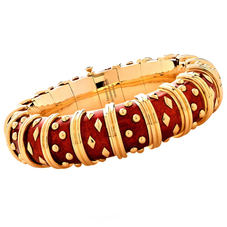 Stunning Tiffany & Co. Schlumberger Dot Losange Bracelet, crafted in 18k yellow gold and enriched with vibrant crimson red enamel, accented with alternating clusters of gold dots and diamond shapes, separated by gold rings. The bracelet measures .7