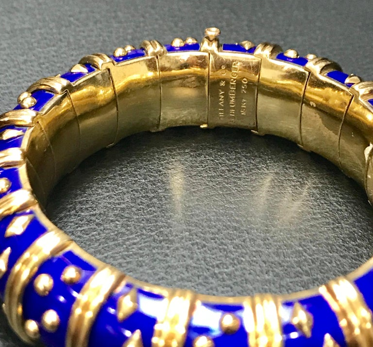Stunning Tiffany & Co. Schlumberger Dot Losange Bracelet, crafted in 18k yellow gold and enriched with vibrant  blue enamel, accented with alternating clusters of gold dots and diamond shapes, separated by gold rings. The bracelet measures 2 cm in