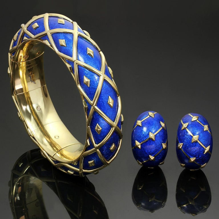 This chic set from the Dot Losagne collection by Tiffany & Co. features a bangle bracelet and a pair of matching clip-on earrings crafted in 18k yellow gold and blue enamel. Designed by Schlumberger  circa 1990s. Please see a small spot with enamel