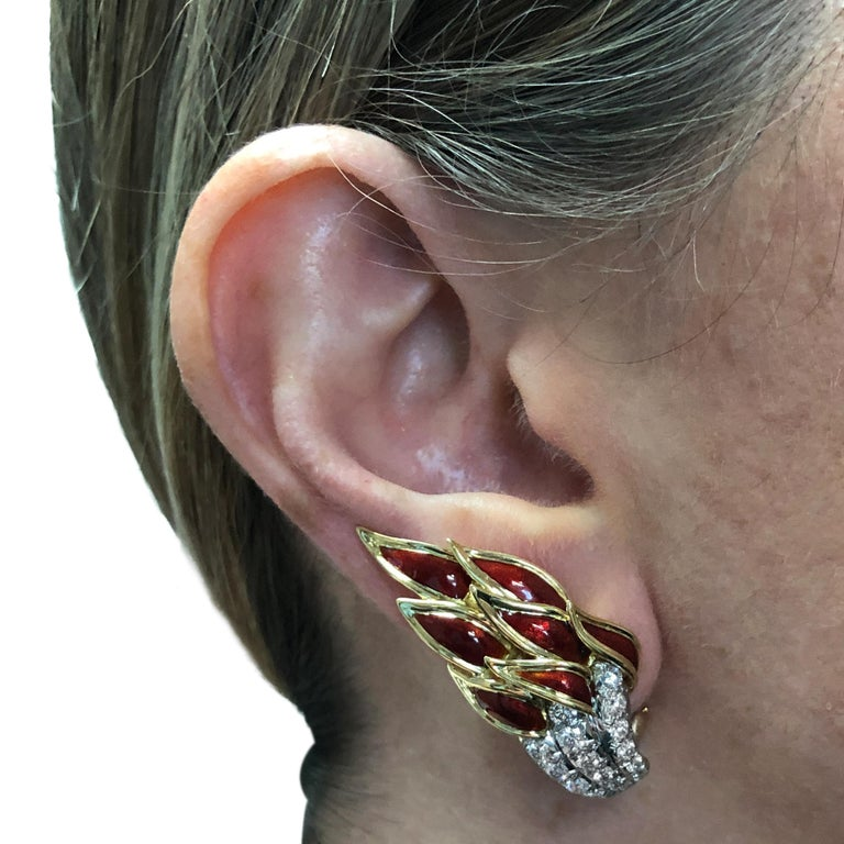 Spectacular Tiffany and Co. Schlumberger Flame earrings, crafted in 18 karat yellow gold, platinum and red enamel, featuring 34 round brilliant cut diamonds weighing approximately 2 carats total, F color, VS clarity. These stunning earrings catch