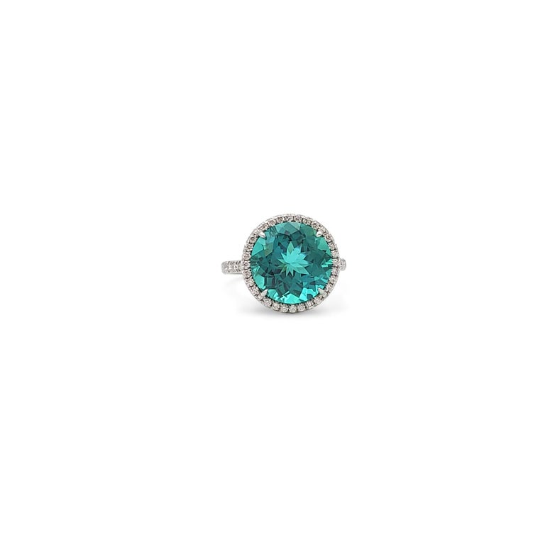 Authentic Tiffany & Co. 'Soleste' ring centers on a round faceted bluish-green tourmaline stone weighing 6.29 carats. The lively neon bluish-green gemstone is mounted in a delicate platinum mounting that is pave set with an estimated 0.75 carats