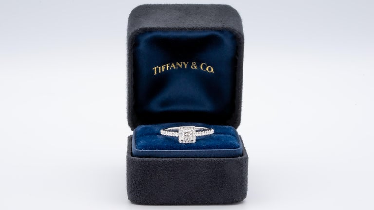 Tiffany & Co. Soleste Diamond Engagement ring featuring a .36 ct Princess Cut Center diamond finely crafted in Platinum, accented by a bead set diamond halo and shank with 36 round brilliant cut diamonds weighing 0.25 cts. total weight for a total