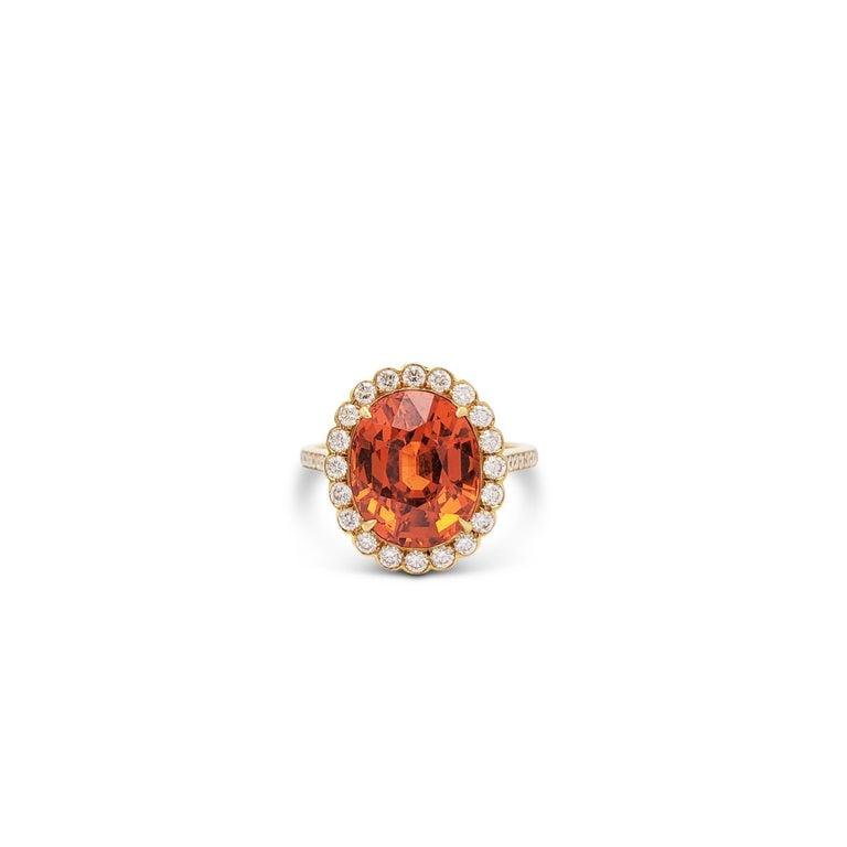 An authentic Tiffany & Co. ring crafted in 18 karat yellow gold centering on a striking orange-hued natural spessartite garnet weighing 6.11 carats which is highlighted by a halo of round brilliant cut diamonds (E-F color, VS clarity) weighing an