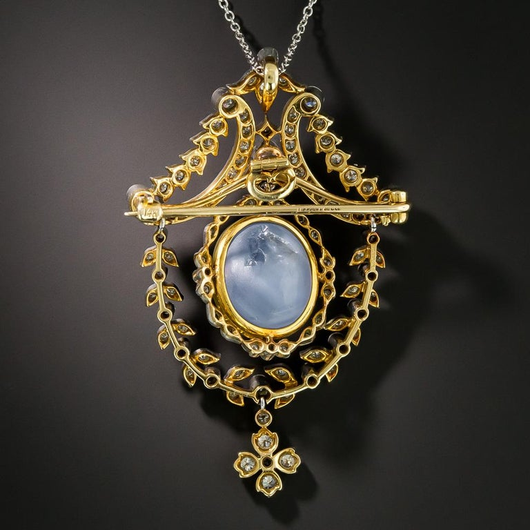 A superb and extravagant early 20th century work of art from Tiffany & Co. A large and luminous periwinkle blue cabochon star sapphire, weighing 25 carats and set in a gold bezel, floats in a surround of glittering diamonds and suspends from an