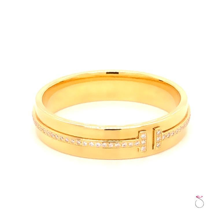 Authentic Tiffany & Co. T Wide Diamond Band Ring, 18K Yellow Gold. This striking ring features a bold