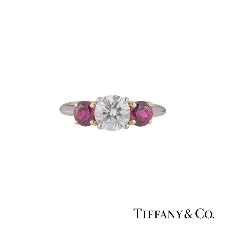 A luxurious platinum and 18k yellow gold Tiffany & Co. diamond and ruby ring from the Three Stone with Ruby collection. The ring comprises of a round brilliant cut diamond in a 4 claw setting in a platinum band. Complementing the centre diamond are