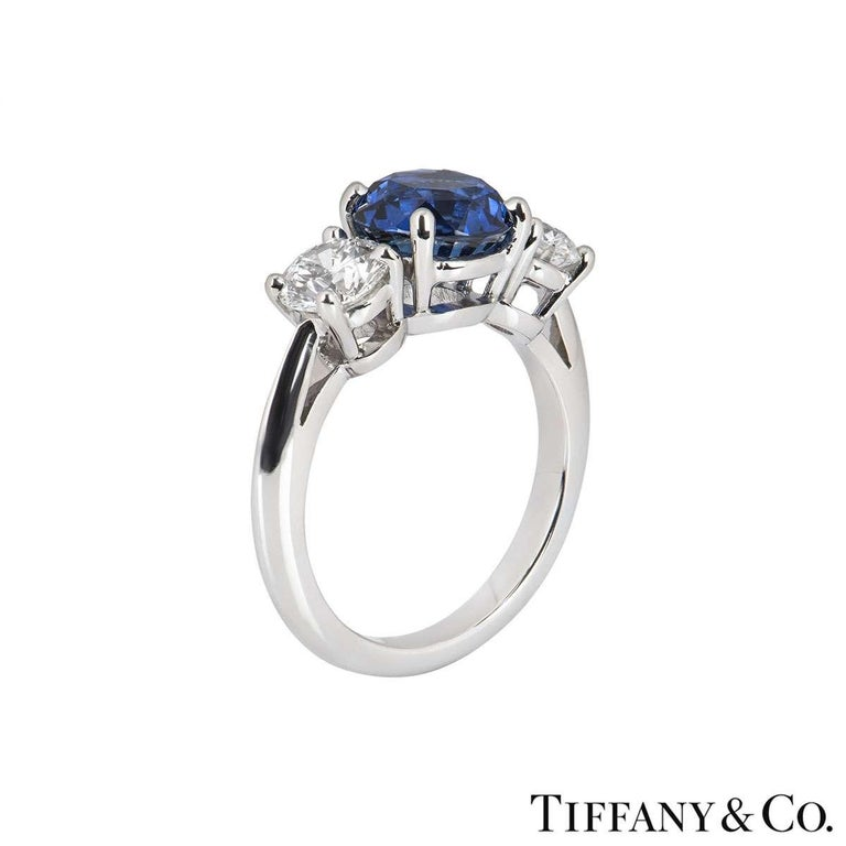 A luxurious platinum Tiffany & Co. diamond and sapphire ring from the Three Stone with Sapphire collection. The ring comprises of a round brilliant cut sapphire in a 4 claw setting in a platinum band. The sapphire has a weight of 1.25ct, with a deep