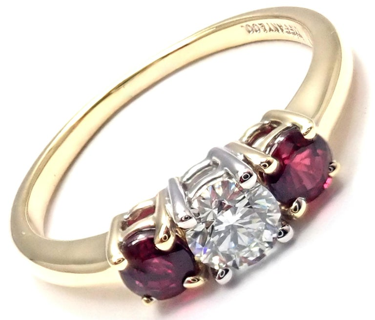 18k Yellow Gold and Platinum Diamond And Ruby Three Stone Band Ring by Tiffany & Co.  With 1 Round Brilliant Cut Diamond VS1 clarity, G color, Total weight Approx .50ctw 2 Round rubies total weight approx.  0.50ct Details: Ring Size: 6 Width: