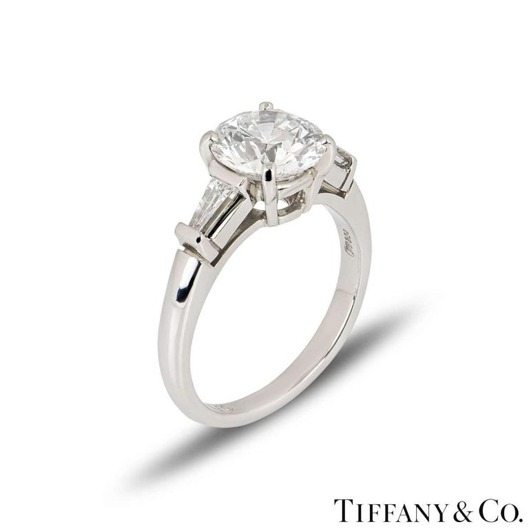A stunning Tiffany & Co. diamond platinum engagement ring from the Three Stone collection. The ring comprises of a round brilliant cut diamond in a 4 claw setting weighing 2.10ct, E colour and VS1 clarity. Flanked by two tapered baguette cut