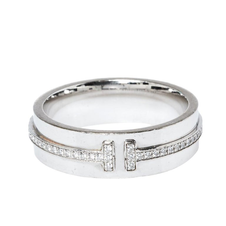 Highlighting the letter 'T' in a charming way with diamonds is this ring by Tiffany & Co. It comes in a wide 18k white gold body with the 'T' running along the center. The ring is from the Tiffany T collection which is characterized by clean lines
