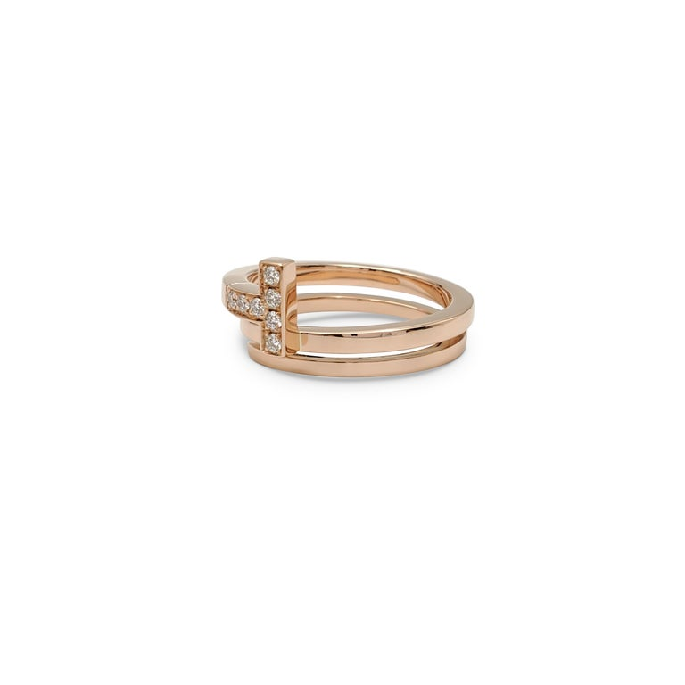 Authentic Tiffany & Co. 'Tiffany T' square wrap ring crafted in 18 karat rose gold and accented with an estimated 0.10 carats of high quality (E-F color, VS clarity) round brilliant cut diamonds. Signed T&Co., Au750, Italy. Ring size 6. The ring is