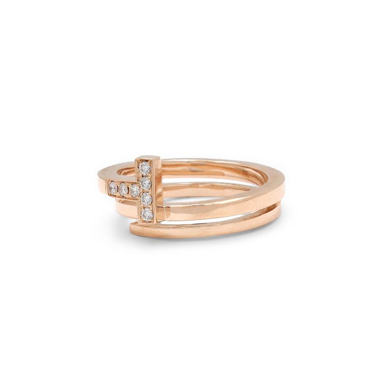 Authentic Tiffany & Co. 'Tiffany T' square wrap ring crafted in 18 karat rose gold and accented with an estimated 0.10 carats of high quality (E-F color, VS clarity) round brilliant cut diamonds. Signed T&Co., Au750, Italy. Ring size 6 1/2 US, 54