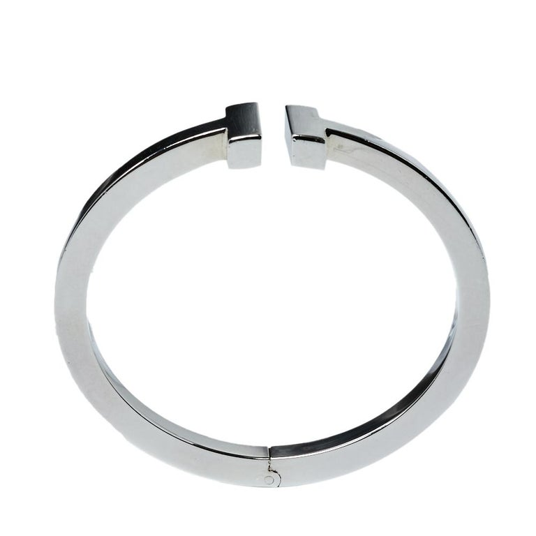 Awe-inspiring and radiating sophistication, this Tiffany T Square bracelet from Tiffany & Co. is a piece that you will always cherish wearing! Crafted from silver 925 metal, it features a smooth band that carries the letter 'T' at both ends. It has