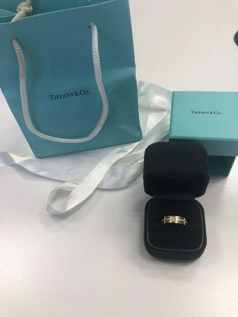 Tiffany & Co 18k Yellow Gold Round Diamond T Shaped Band Ring Size 7.25 7.8 Grams  White Round Brilliant Cut Diamonds 0.12 Carats Total Weight Color: F Clarity: VS2  This is a beautiful Tiffany & Co. diamond band that shows off these round diamonds.