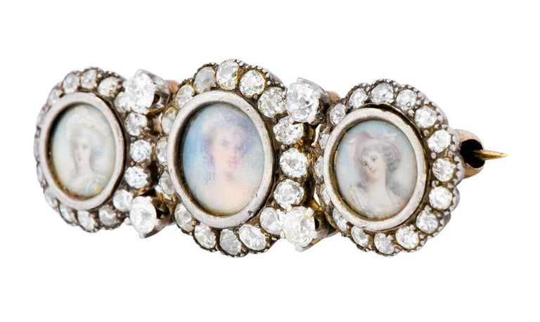 Centering three glass covered, hand painted portraits of women  One with grey curls, a fancy hat, and a blue dress; another with blonde updo and exposed shoulders; and one with large grey curls and white floral Victorian bonnet, all against a blue