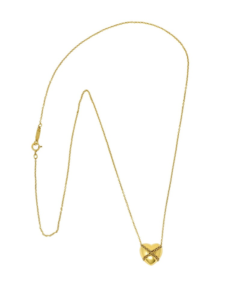 Cable chain necklace suspends a brightly polished puffed heart pendant  Encompassed with a twisted rope motif in a harlequin pattern  Completed by a spring ring clasp  Both stamped 750 for 18 karat gold  Both fully signed Tiffany & Co.  From the