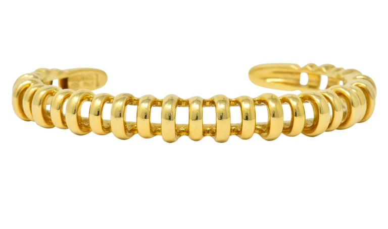 Designed as a high polished cuff   Featuring pierced ribbed design alternating in height, and polished gold terminals  Fully signed Tiffany & Co.  Stamped 750 and Italy  Inner circumference: 5 3/4 inches  Width: 3/8 inch  Total weight: 26.9