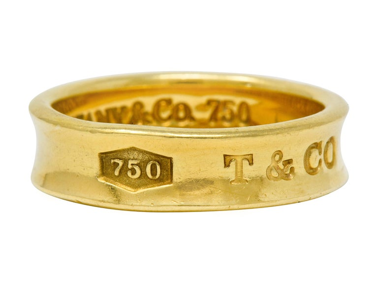 High polished gold band with recessed central groove  Deeply engraved to front 750, T & Co, and 1837  Inner shank fully signed Tiffany & Co. 1997  Stamped 750 for 18 karat gold  From the celebratory Tiffany 1837 collection  Ring Size: 9 1/2 & not