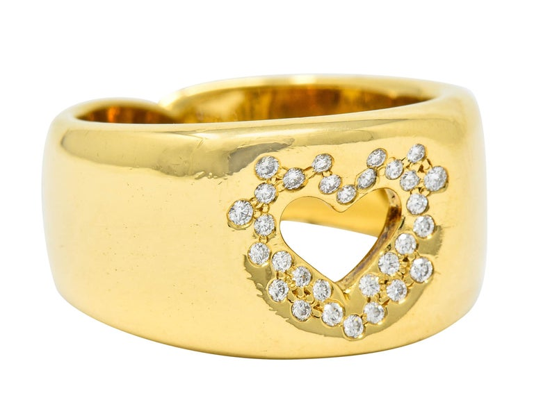 Wide band ring centering a pierced heart motif  Sprinkled with flush set diamonds weighing approximately 0.30 carat; eye-clean and white  Completed by a sweet shank detail at base  Fully signed Tiffany & Co. and stamped 750 for 18 karat gold  Circa: