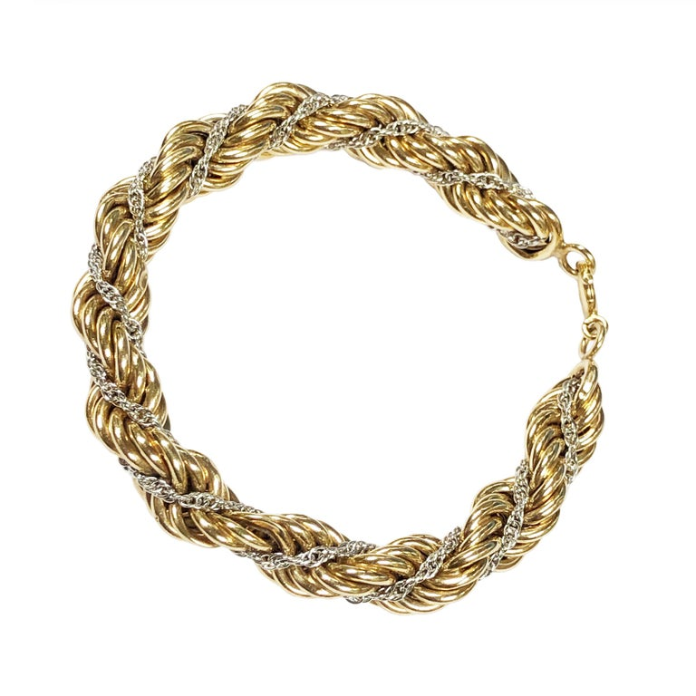 Circa 1980s Tiffany & Company 14K Yellow and White Gold Rope Bracelet comprised of a White gold chain interwoven in the larger Yellow Gold Bracelet, measuring 8 inches in length 3/8 inch wide and weighing 29 Grams. Excellent condition and comes in