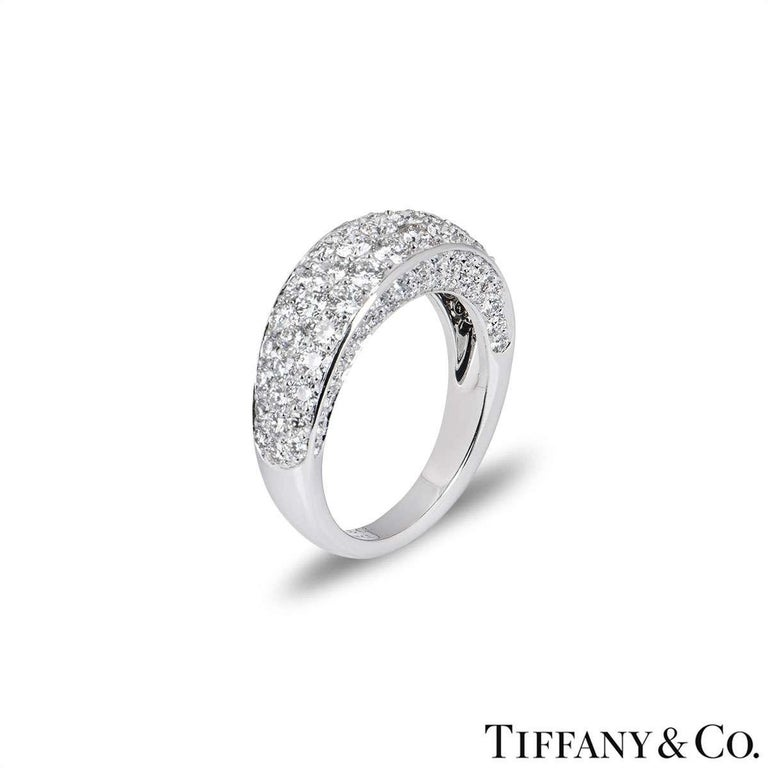 An 18k white gold diamond set ring by Tiffany & Co. The ring is pave set with round brilliant cut diamonds around the front and sides of the band. The ring measures 4mm in height and is a size UK Q / EU 57 / US 8, with a gross weight of 8.2