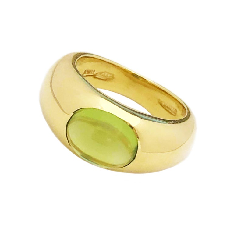 Circa 1970s Tiffany & Company 18K Yellow Gold Ladies Ring, centrally set with a fine color Oval Cabochon Peridot, measuring 8 X 6 MM approximately 2 Carats. Measuring 5/8 inch across the top and 1/4 inch wide. Finger size 4.