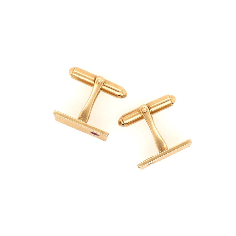 A pair of 14 karat yellow gold and ruby cufflinks with spring links, circa 1940s, Tiffany.  The face of each rectangular cufflink is set with a 3mm round faceted ruby toward one end, with a sunray pattern radiating from around the ruby.  Each