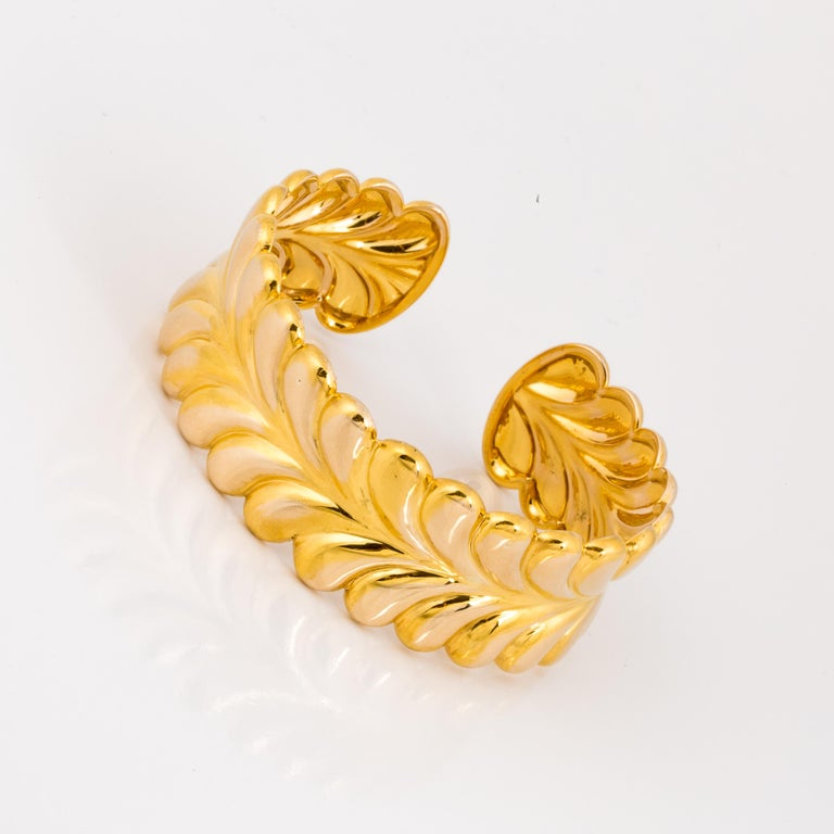 14K yellow gold bracelet made by Tiffany & Co.  The cuff has an interlocking feather design.  It measures 1