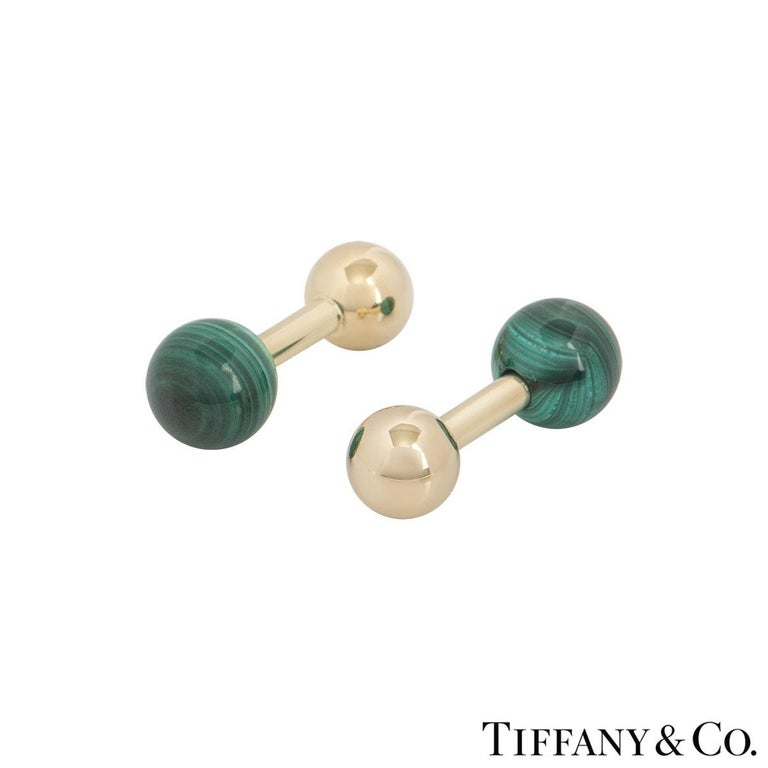 A pair of 14k yellow gold malachite ball cufflinks by Tiffany & Co. The cufflinks each feature a malachite bead on one end and a yellow gold polished ball on the other. The cufflinks are encased together by a bar fitting with a length of 2.70cm with