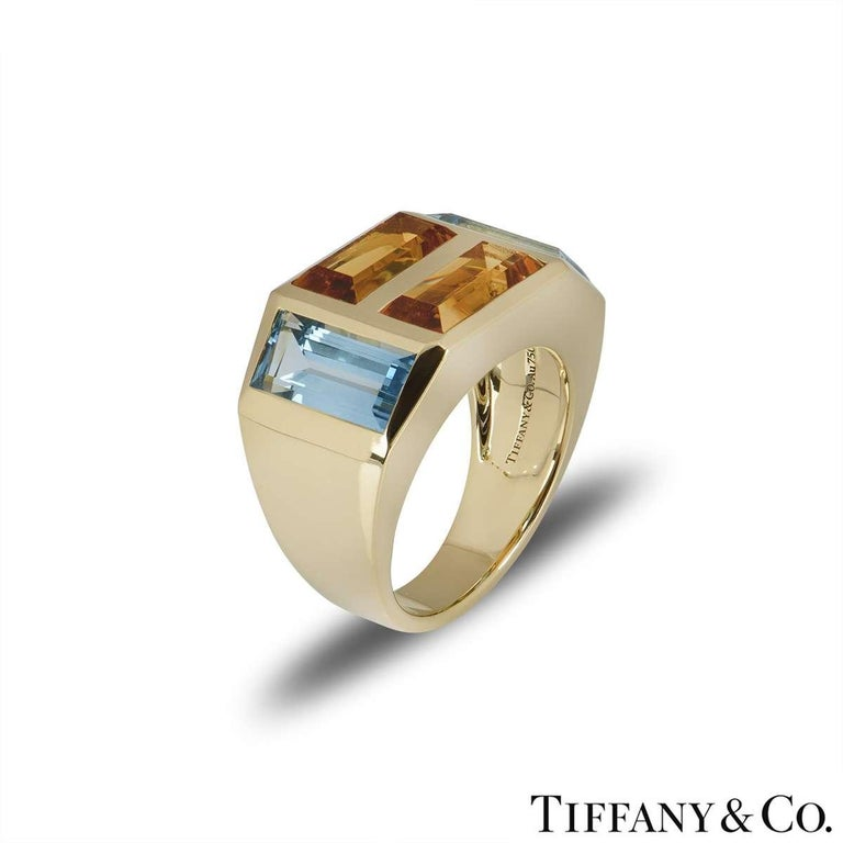 A beautiful 18k yellow gold dress ring from the Paloma Picasso collection by Tiffany & Co. The ring is set with two emerald cut citrine's set horizontally and two emerald cut blue topaz stones set vertically on either side. The citrine's have a