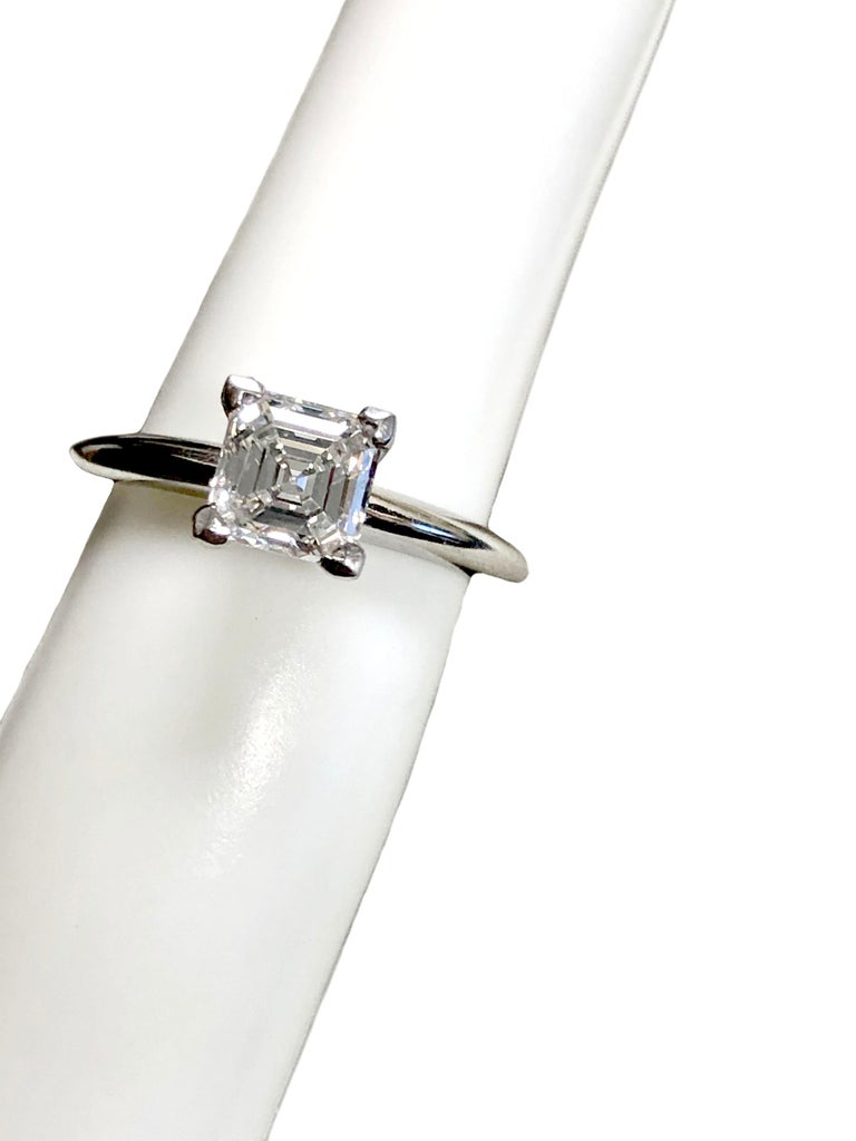Tiffany & Company Engagement Ring, 2 M.M. wide Platinum mounting with a 4 prong head, set with a 1 Carat Square Emerald cut Diamond G.I.A. graded as G in color and VVS1 in clarity. Finger size 4 1/2 this ring is new unworn, comes in the original