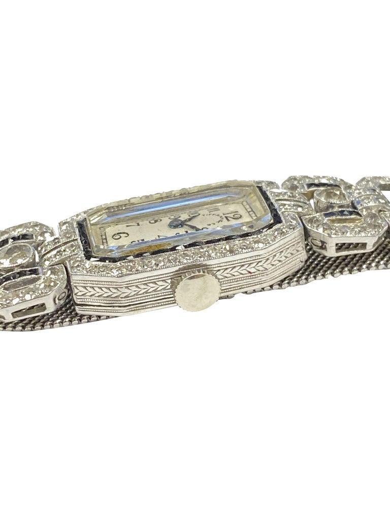 Circa 1920s Tiffany & Company Ladies Platinum Diamond and Onyx Bracelet Watch, the watch itself measures 22 X 14 M.M. and is a 2 piece Platinum case with hinged back and hand engraved design work throughout.  17 jewel Glycine, Mechanical, manual