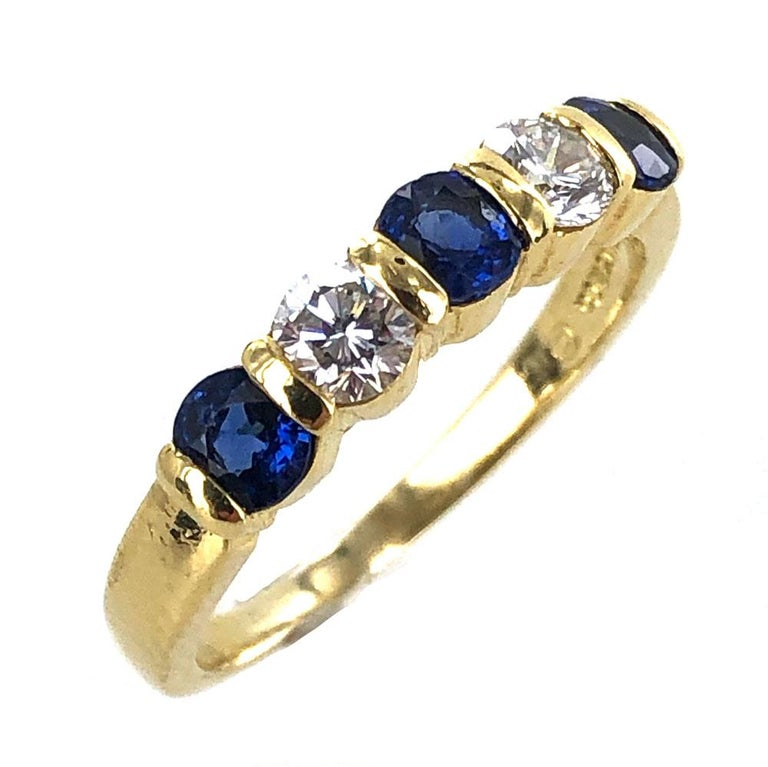 Stunning diamond and sapphire band by Tiffany & Co. The band features 2 round brilliant cut diamonds graded F color and VS1 clarity, and 3 round blue natural sapphires. The ring is currently size 7.75. Signed Tiffany & Co. 750. Weight: 4.1 grams.