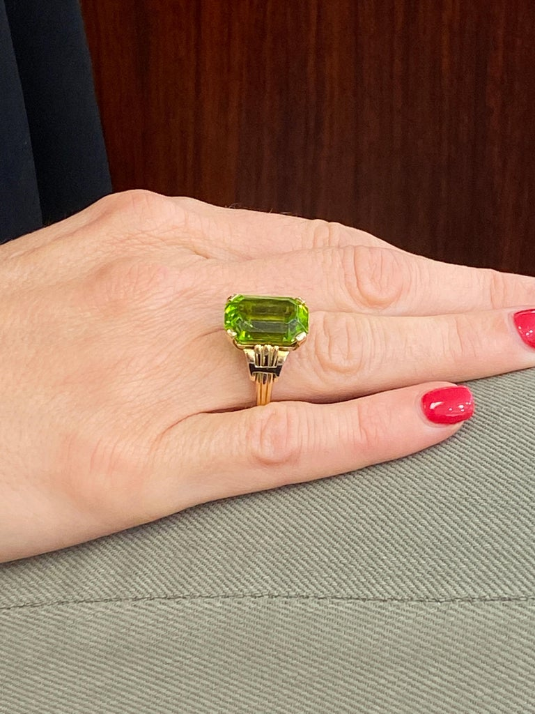 Tiffany & Company Vintage Peridot Ring fashioned in 14 karat yellow gold. The emerald cut peridot gemstone weighs approximately 12 carats, has a beautiful yellowish green color, and has been certified by the AGL. The peridot has not had any