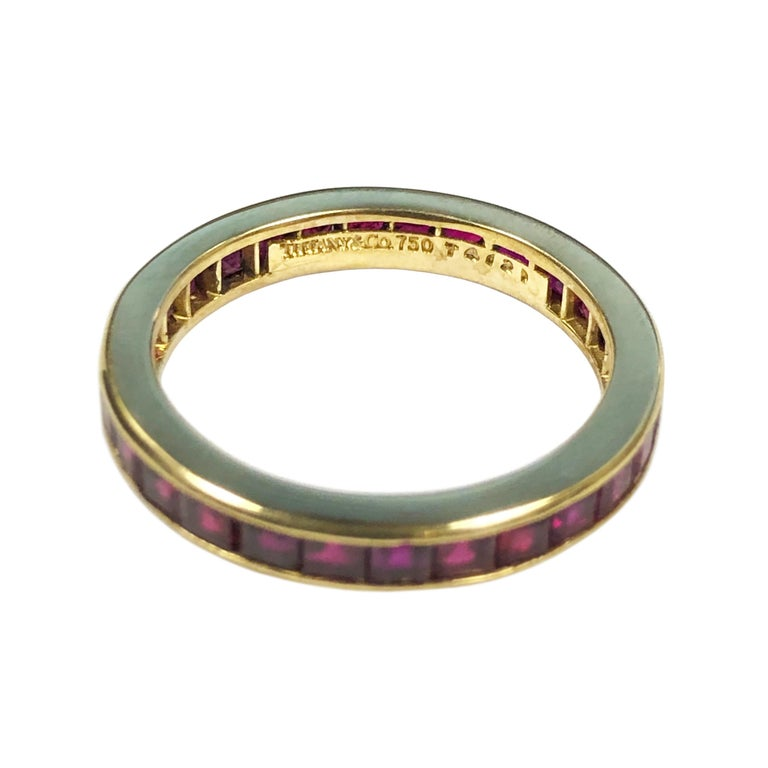Circa 1990s Tiffany & Company 18K Yellow Gold Eternity Band Ring, set with Square cut Rubies of Fine Burma quality color and totaling approximately 1.50 carats. The ring measures 2.5 M.M. wide and is a finger size 7.  Comes in original Tiffany