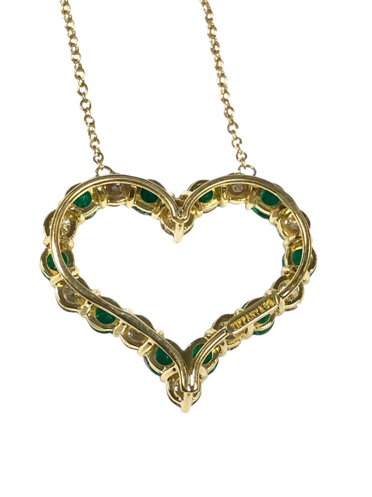Circa 2000 Tiffany & Company 18K yellow Gold Heart Pendant Necklace, the Heart measures 7/8 inch in length X 1/2 inch wide, set with very fine Bright color Emeralds totaling approximately 1.30 Carats and further set with Round Brilliant cut Diamonds