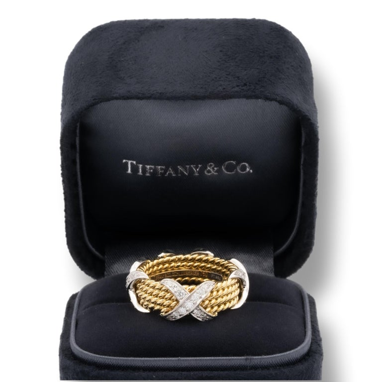 Tiffany & Co. Schlumberger X 4 row rope wide ring finely crafted in 18 karat yellow gold and platinum. The 4 X's are set with 52 round brilliant cut diamonds inside a channel weighing 0.54 carats total weight.    Stamp: Tiffany & Co. Schlumberger