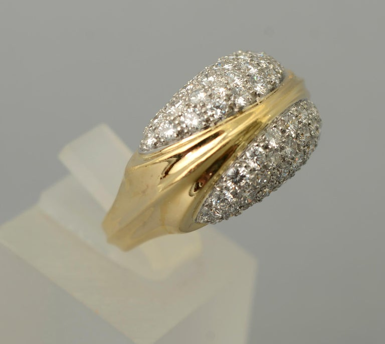Elegant diamond cocktail ring by Tiffany and Co. The 18 karat ring has approximately 3 carats of VS 1 diamonds; H  color. A gold band that is integrated as part of the design of the entire ring separates two groups of diamonds. The ring is size 7