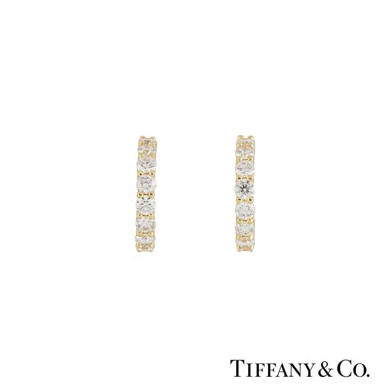 A pair of 18k yellow gold diamond hoop earrings by Tiffany & Co. Each hoop has 10 claw set round brilliant cut diamonds totalling 0.60ct, G colour and VS in clarity. The earrings measure 1.2cm in length and have post and alpha back fittings, with a