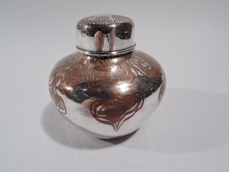 Exotic mixed metal tea caddy. Made by Tiffany & Co. in New York, circa 1910. Sterling silver ginger-jar with squat and tapering sides, short neck, and snug-fitting cover. Copper ornament with irregular scrollwork. Fully marked including pattern no.