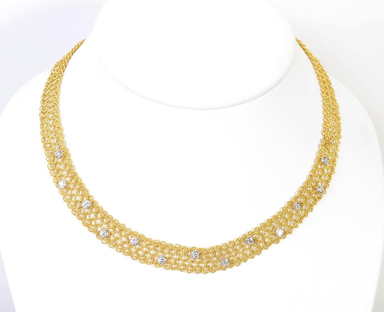 Exquisite and  delicate gold and diamond choker necklace by Tiffany. The length of the necklace is made of fine, interlocking circles of twisted gold. It is half an inch wide and 16 1/4 inches long. Set atop the gold are 13 round diamonds with a