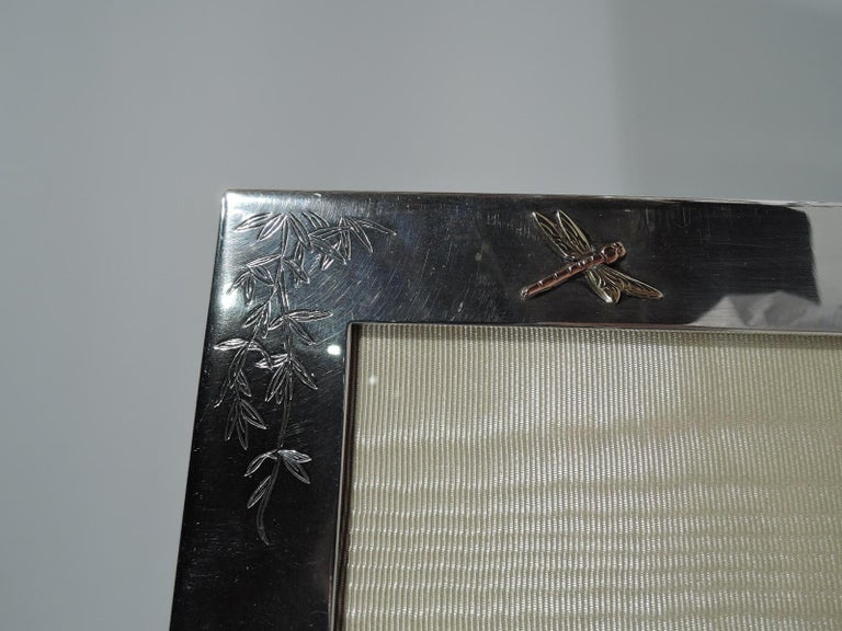 Japonesque revival sterling silver and mixed metal picture frame. Made by Tiffany & Co in New York, circa 1970. Rectangular window and flat surround with engraved bamboo and mixed metal appliques, including a dragonfly – a perennial symbol of the