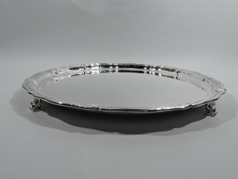 Edwardian Classical sterling silver tray. Made by Tiffany & Co. in New York, ca 1925. Round well. Rim has long and gently scrolls inset with rope border and Classical volute terminals interspersed with scallop shells. Four dolphin-style volute